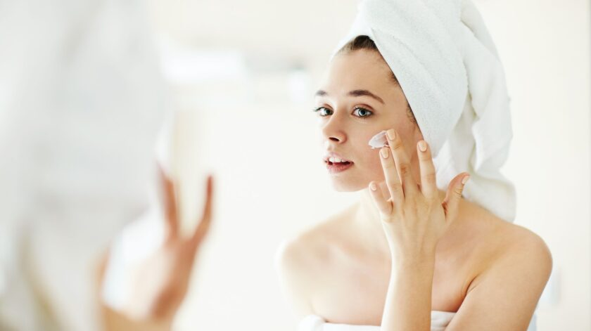 Pretty girl applying moisturizing cream in front of mirror
